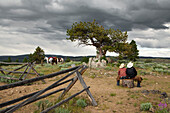 USA, Wyoming, Encampment, two women wranglers sit on a log at the top of a mountain, Abara Ranch