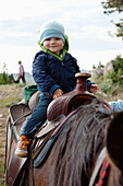 USA, Wyoming, Encampment, a young boy sits on a horse for the first time, Abara Ranch