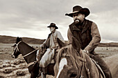 USA, Wyoming, Encampment, cowboys on horseback get ready to round up cattle for a branding, Big Creek Ranch (B&W)