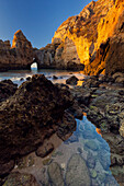 The Algarve rocks radiating a yellow glow in the morning sunlight with crystal-clear water of the Atlantic Ocean and a clear blue sky, Algarve, Portugal