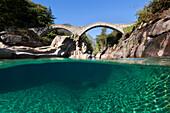 View beneath the water surface of the mountain river Verzasca near Lavertezzo with the historic bridge Ponte dei Salti in the Swiss Alps, Canton of Ticino, Switzerland