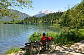 Cyclist taking a rest at Lake Barmsee, Karwendel mountain range near Kruen, Bavaria, Germany