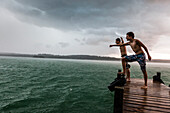 Two young men on a jetty leaning into the wind, Lake Starnberg, Bavaria, Germany