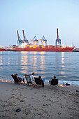 Guests on the beach near Cafe Strandperle in Hamburg-Oevelgoenne, the HHLA container terminal is situated on the opposite bank of the Elbe, Hamburg harbour, Hamburg, Germany