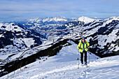 Female back-country skier ascending to Grosser Schuetz, Kaiser mountain range in background, Kitzbuehel Alps, Tyrol, Austria