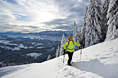 Female backcountry skier ascending to Kranzhorn, Kaiser Mountain Range in background, Chiemgau Alps, Tyrol, Austria