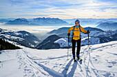 Female backcountry skier ascending to Grosser Traithen, Kaiser mountain range in background, Mangfall range, Bavarian Alps, Upper Bavaria, Bavaria, Germany
