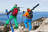 Two skiers looking over Lake Tahoe, Heavenly ski resort, California, USA