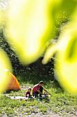 Father and son having breakfast in front of a tent, near Boitzenburg, Uckermark, Brandenburg, Germany