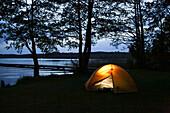 Illuminated tent at lakeside, Lychen, Uckermark Lakes Nature Park, Uckermark, Brandenburg, Germany