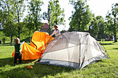 Mother and son (2 years) putting up a tent, Wesenberg, Mecklenburg-Western Pomerania, Germany
