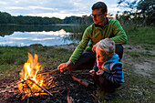 Father and son (2 years) near a campfire at lakeside, near Blumenholz, Mecklenburg-Western Pomerania, Germany