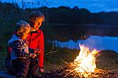 Mutter und Sohn (2 Jahre) am Lagerfreuer an einem Seeufer, bei Blumenholz, Mecklenburg-Vorpommern, Deutschland