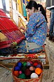 Bhutan (kingdom of), District of Paro, the City of Paro, in Chencho Handycraft shop, Mrs Chuki Wangmo and her very nice daughter Tandin Bidha, a movie actress, weaver at loom weaving traditional fabric // Bhoutan (Royaume du), district de Paro, la ville d
