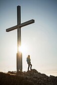 Hiker standing by cross on rocky hilltop. Branderschrofen, Tegelberg