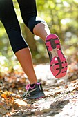 The back view of legs of a woman wearing work-out clothing jogging on a trail in a forest setting in the fall
