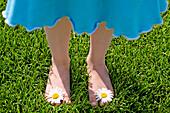 Close-up of young girl standing on lawn with daisies between toes.
