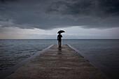 Man with Umbrella Standing on Pier, Woodbine Beach, Toronto, Ontario