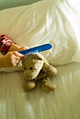 Boy Combing Teddy Bear