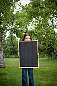 Girl on Apple Farm holding Blank Chalkboard