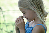 Young Girl Holding Frog to her Nose
