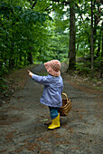 Little Girl in a Rain Coat and Rubber Boots with a Basket Pointing to Trees on a Trail, Lake Muskoka, Bracebridge, Ontario