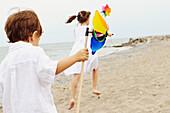 Brother and Sister Running along a Beach Holding Pinwheels, Toronto, Ontario