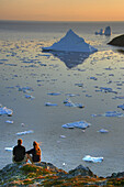Couple looking out at an Iceberg at Sunset, Twillingate, Newfoundland