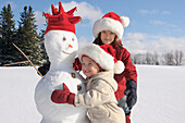 Brother and Sister Playing with Snowman