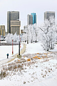 Downtown skyline and man jogging on winter day, Winnipeg, Manitoba