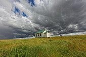 Man walking to abandoned church, with storm clouds overhead, Saskatchewan