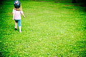 Blond girl with bike helmet running in park, Otterburn Park, Quebec