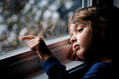 Young boy looking out a window and scratching the glass, Otterburn Park, Quebec