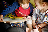 Brother and sister in pajamas reading a book, Otterburn Park, Quebec