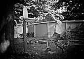 Boy playing in yard with a toy basketball set, Otterburn park, Quebec