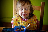 Little girl at table with bowl of cereal and eyes closed, Otterburn, Quebec