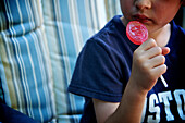 Boy eating a red lollipop, Otterburn, Quebec