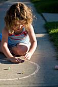 Young girl playing with marbles on the sidewalk, Regina, Saskatchewan