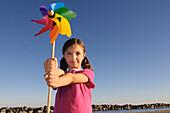 Girl Standing on Beach Holding Pinwheel, Toronto, Ontario