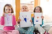 Three little girls holding artwork, Toronto, Ontario