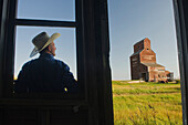 Farmer looking towards an abandoned grain elevator, in the ghost town of Bents, Saskatchewan