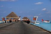Republic of the Maldives, Lhaviyani Atoll,  Kanuhura Hotel, woman walking on the landing stage