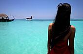 Republic of the Maldives, Lhaviyani Atoll,  Kanuhura Hotel, rear view of a woman looking at a seaplane