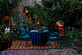 Romantic Ambiance, Wrought iron garden furniture with carpets and candle jars in a private garden at dusk