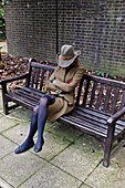 England, London, Elegant young woman with a hat falling asleep on a public bench