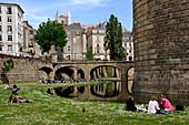 'France, Pays de la Loire, Nantes, Château des Ducs de Bretagne - ''Castle of the Dukes of Brittany'', rue Prémion, People resting on the lawn of the moats'