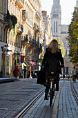France, Bordeaux, Southwestern France, Aquitaine, rue Vital Carles, Woman cycling on a tram track