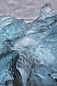A close-up view of glacial ice strewn across a coastal beach, iceland