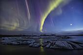 Aurora borealis dances over the glacial lagoon jokulsarlon, iceland