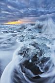 Waves from the atlantic ocean crash into ice calf from breioamerkurjokull a glacial tongue of the vatnajokull ice cap, iceland